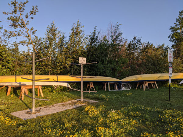 Two long yellow boats on sawhorses next to two boat racks