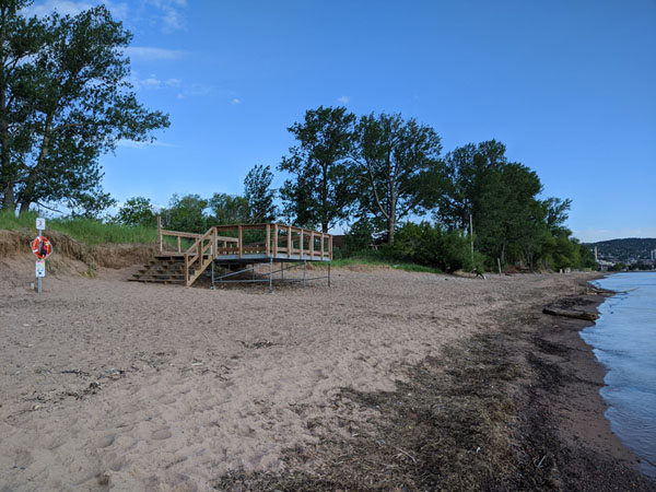 Sandy beach with wooden stairway and trees in background