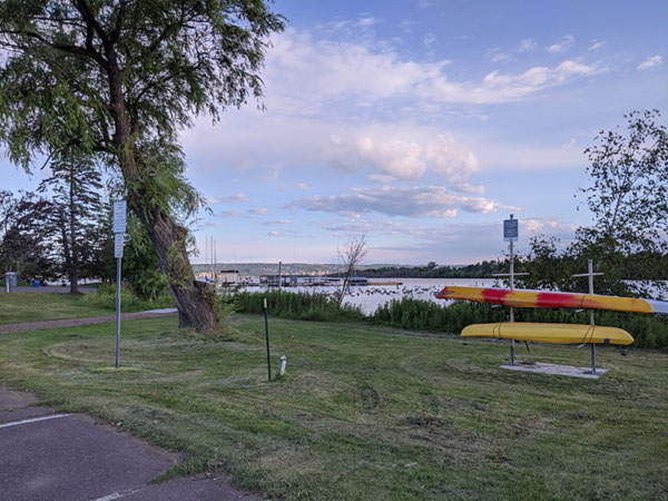 Grassy area with boat rack holding two yellow kayaks. Lake in background.